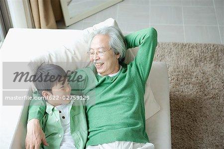 Homme senior avec petit-fils reposant sur canapé