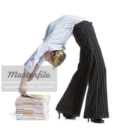 Female contortionist businesswoman bending over backwards