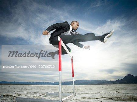 Flachwinkelansicht eines Kaufmanns Sprung über eine Hürde in einem Rennen