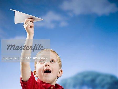 Junge mit Papierflieger im freien