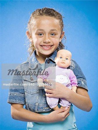 Jeune fille tenant un bébé poupée souriant