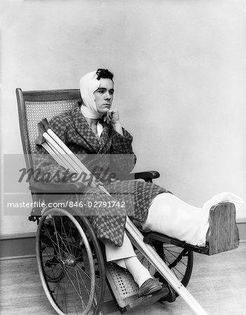 1930s MAN IN WHEELCHAIR LEG CAST BANDAGE HEAD NECK CRUTCHES BROKEN INVALID DEPRESSED HURT PAIN INJURY