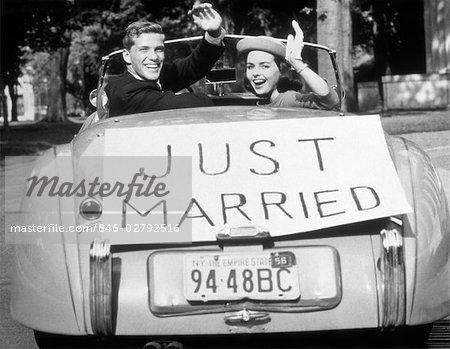 DES ANNÉES 1950 LA JEUNE MARIÉE JEUNE COUPLE HOMME FEMME DANS LA VOITURE DE SPORT CONVERTIBLE AVEC JUST MARRIED SIGN AGITANT REGARDANT LA CAMÉRA