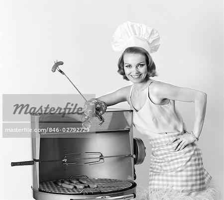 FEMME DES ANNÉES 1960 PORTANT CHEF HAT STANDING AT BBQ GRILL TENANT UNE FOURCHE AVEC HOT DOG