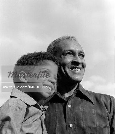 ANNÉES 1970 SOURIANT NOIR GARÇON & GRAND-PÈRE AVEC BRAS AUTOUR DE L'AUTRE À LA RECHERCHE HORS TENSION À DISTANCE