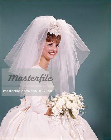 1960ER JAHREN SITZEND LÄCHELND GLÜCKLICHE BRAUT PORTRAIT WHITE WEDDING GOWN BRAUTSTRAUSS-BLUMEN KURZ NET SCHLEIER