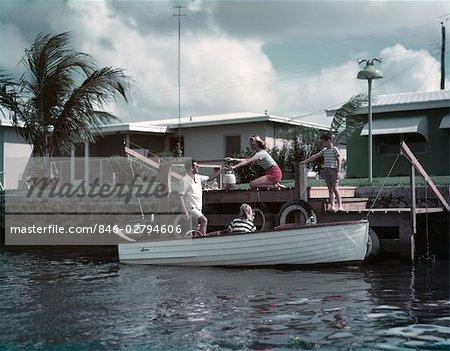 ANNÉES 1950 FAMILLE CHARGEMENT PIQUE-NIQUE EN PETITS BOIS MOTEUR BATEAU DÉRIVEUR MAMAN PAPA GARÇON FILLE HOMME FEMME DOCK TROPICAL PALM HOUSE