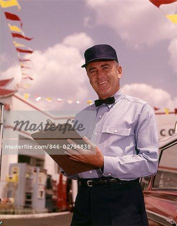 1950s 1960s MAN GAS SERVICE STATION MECHANIC HOLDING CHECK LIST ON CLIPBOARD BLUE UNIFORM HAT BLACK BOW TIE SMILING