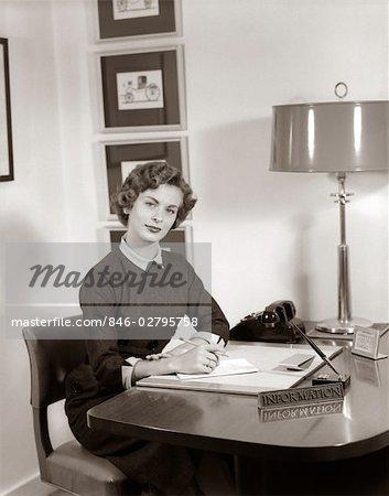 RÉCEPTIONNISTE DES ANNÉES 1950, ASSIS AU COMPTOIR AVEC PANNEAU D'INFORMATION NOTE PAD & CRAYON BEHIND