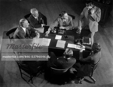 ANNÉES 1930 SIX HOMMES ET UNE FEMME ASSIS AUTOUR DE PC DE BUREAU TOUT EN UN HOMME PARLE ON TÉLÉPHONE