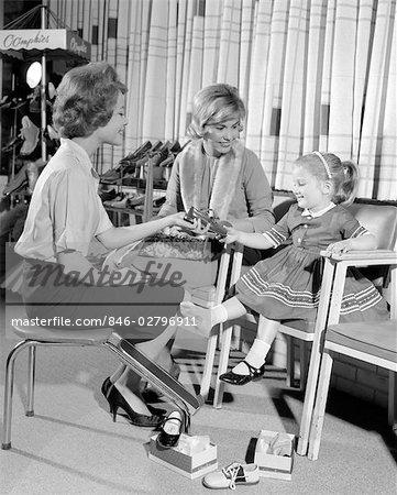 ANNÉES 1960 MÈRE FILLE CHAUSSURES SHOPPING VENDEUSE AFFICHAGE DE CUIR VERNI CHAUSSURE GIRL IN RETAIL STORE