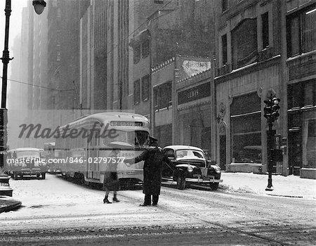 ANNÉES 1940 POLICIER STREET SCENE HIVER FEMME AIDANT PIÉTONNE TRAVERSER SNOWY RUE PASSÉ EN ATTENTE DE VOITURE DE CHARIOT ET AUTOMOBILES