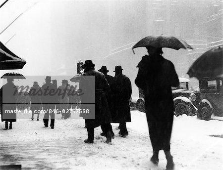 ANNÉES 1930 FOULE DES PIÉTONS DANS LA NEIGE ORAGE MARCHANT DANS UNE VILLE RUE FEUX PARAPLUIES