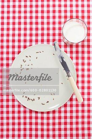 Assiette vide avec un couteau et verre de lait