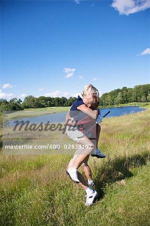 Golfeurs enthousiastes étreignant et acclamations