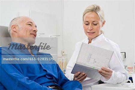 Ein Zahnarzt sprechen für einen Patienten in einem Zahnarztstuhl sitzen