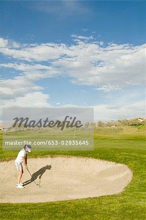 Ein Golfer spielen aus einem Sand-bunker