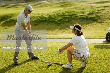 A golf instructor advising a golfer