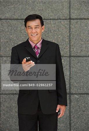 Homme d'affaires tenant le téléphone, regardant la caméra