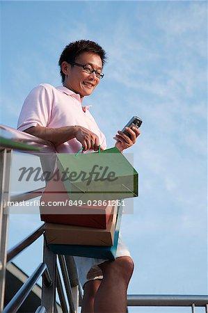 Homme avec des sacs à provisions avec GSM