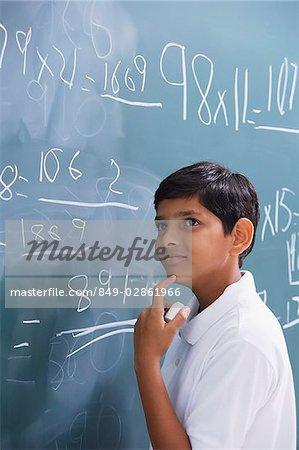 boy at chalkboard, finger on chin