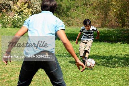 Père et fils de botter le ballon de soccer