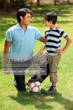 Père et fils avec le pied sur le ballon de soccer