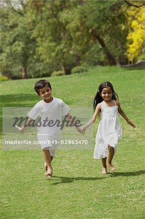 deux petits enfants qui traverse un parc main dans la main