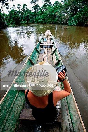 Malaysia, Sarawak, Gunung Mulu National Park, tourist with video camera on river boat trip