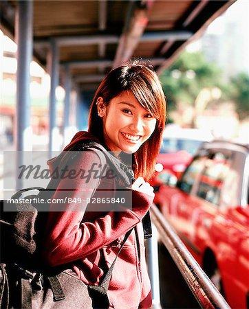 Jeune femme avec sac à dos au taxi stand, portrait.