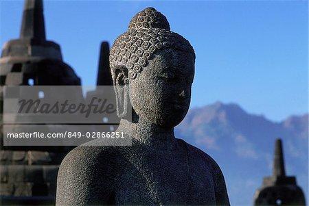Indonesia, Java, Buddha figure at Borobudur temple, mountains in background