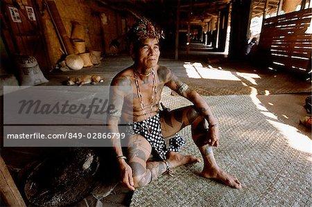 Malaysia, Sarawak, Iban man in traditional dress sitting inside long house