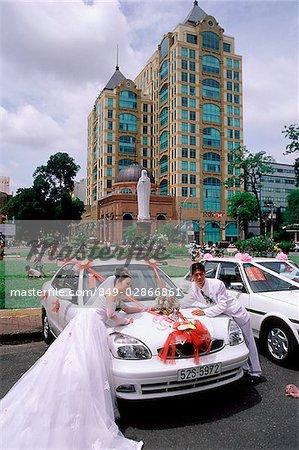 Vietnam, Ho Chi Minh-ville, une mariée et marié se penchant sur les voitures décorées.