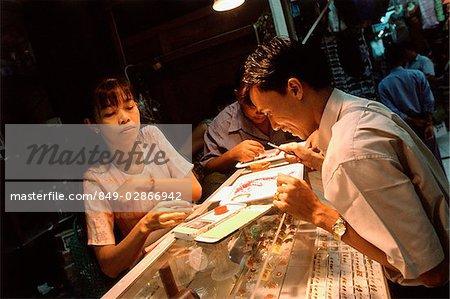 Myanmar (Burma), Yangon (Rangoon), A shopper considering gemstones in Bogyoke Aung San Market, commonly known as Scott's Market.