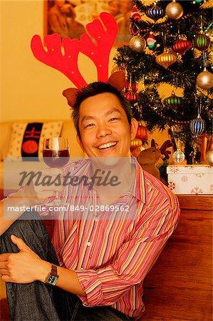 Mann sitzt neben Weihnachtsbaum, Rentier Geweih, das Weinglas heben ...