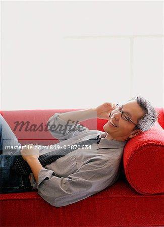 Homme en chemise et cravate, couché sur le canapé, à l'aide de téléphone portable