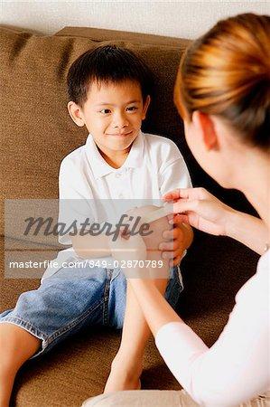Mère mettre un bandage sur le genou de fils