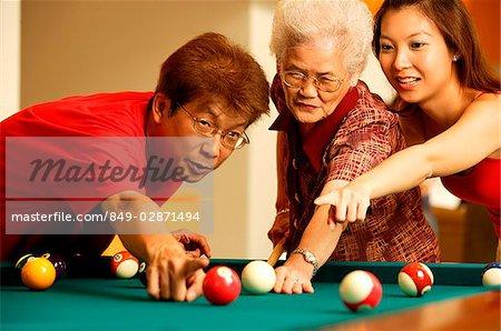 Père et la grand-mère d'enseignement fille à jouer au billard