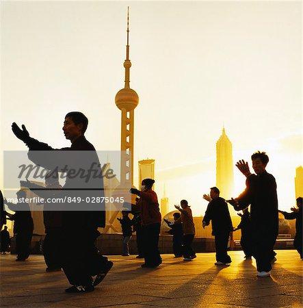 Gens de Chine, Shanghai, faisant de Tai-Chi, en face de Pudong, skyline de quartier d'affaires, à l'aube