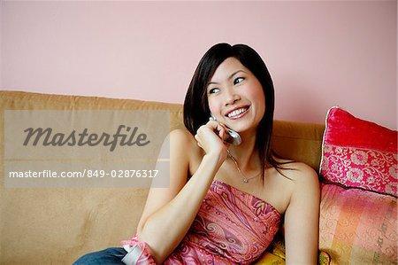 Femme assise sur le canapé, à l'aide de téléphone portable