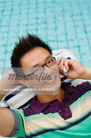 Homme à l'aide de téléphone portable, souriant, piscine en arrière-plan