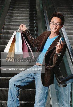 Homme sur l'escalator, porter les sacs et de tenir le téléphone mobile, souriant à la caméra