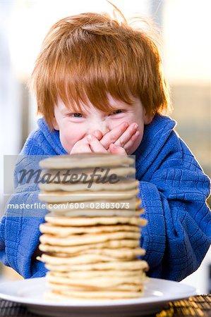 Glücklich kleiner Junge mit einem Stapel von Pfannkuchen