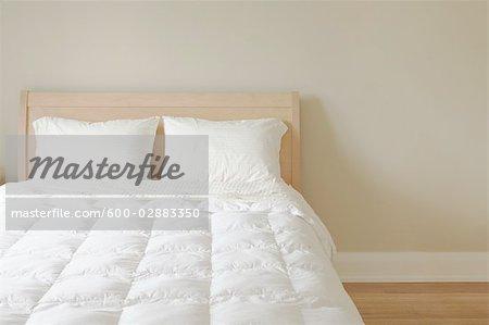 Moderne Reine taille lit blanc literie dans la chambre éclairée