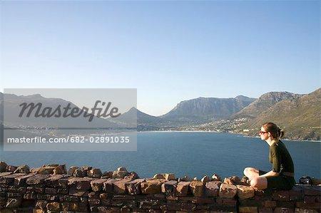 Vue de profil d'une jeune femme assise à côté Peak drive de Chapman à Hout Bay dans la fond, Cape Town, Western Cape Province, Afrique du Sud