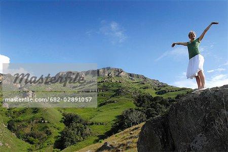Une jeune femme aux bras levé ressemble à travers une vallée, Midlands de Natal, en Afrique du Sud