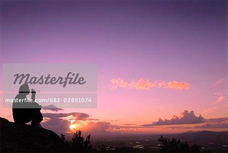 Silhouette d'une femme assise, boire un verre de vin au coucher du soleil, Somerset West, Province du Western Cape, en Afrique du Sud