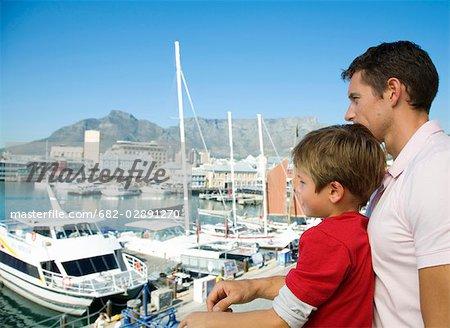 Jeune garçon et son père en regardant bateaux de front de mer et la montagne de la Table dans arrière-plan, Cape Town, Western Cape Province, Afrique du Sud