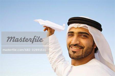 Porträt des Mannes in traditionell orientalische Kleidung hält Papier Flugzeug, Dubai, Vereinigte Arabische Emirate