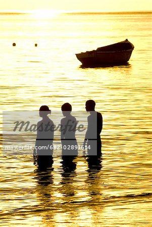Silhouettes de trois personnes debout dans la mer au coucher du soleil, île Maurice